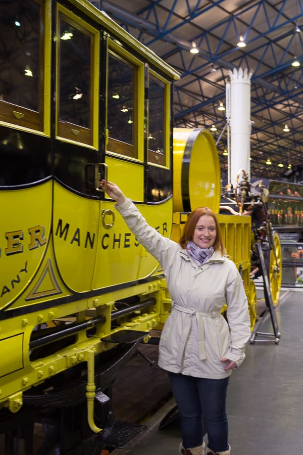 Lynne Lockier with hand on the door of a carriage of the model replica of Stevenson's Rocket.