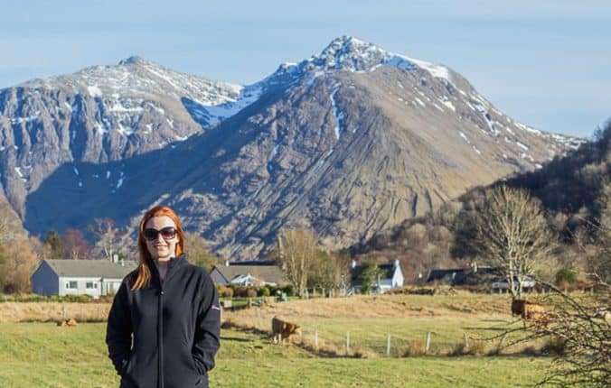 Lynne Lockier standing in Glencoe village with The Pap of Glencoe in the background.