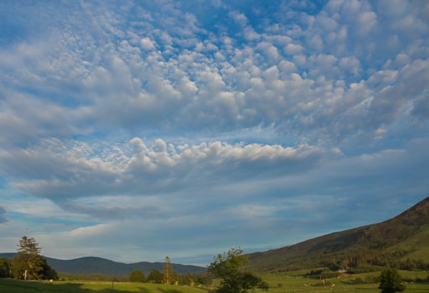 Picture of the blue evening sky and fluffy clouds looking down Glen Clova.