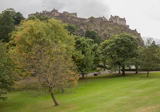 Edinburgh Castle pictured from Princes Street Gardens with autumn leaves on the trees.