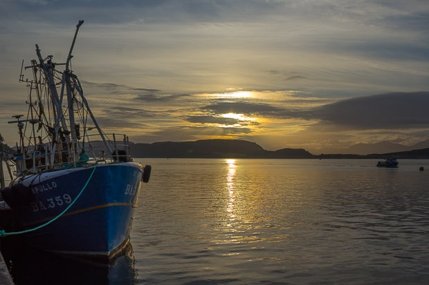 Sunset over Oban harbour with a fishing boat to the left of the picture.