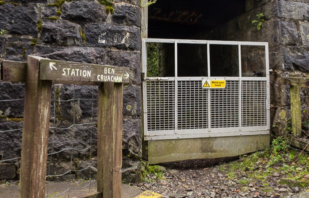 Railway underpess at Falls of Cruachan Railway station. Signpost pointing to the left for the station and to the right for Ben Cruachan.