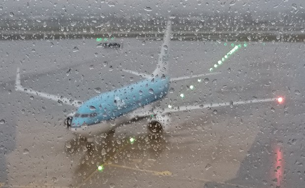 A KLM airplane seen through the wet window at Glasgow airport.