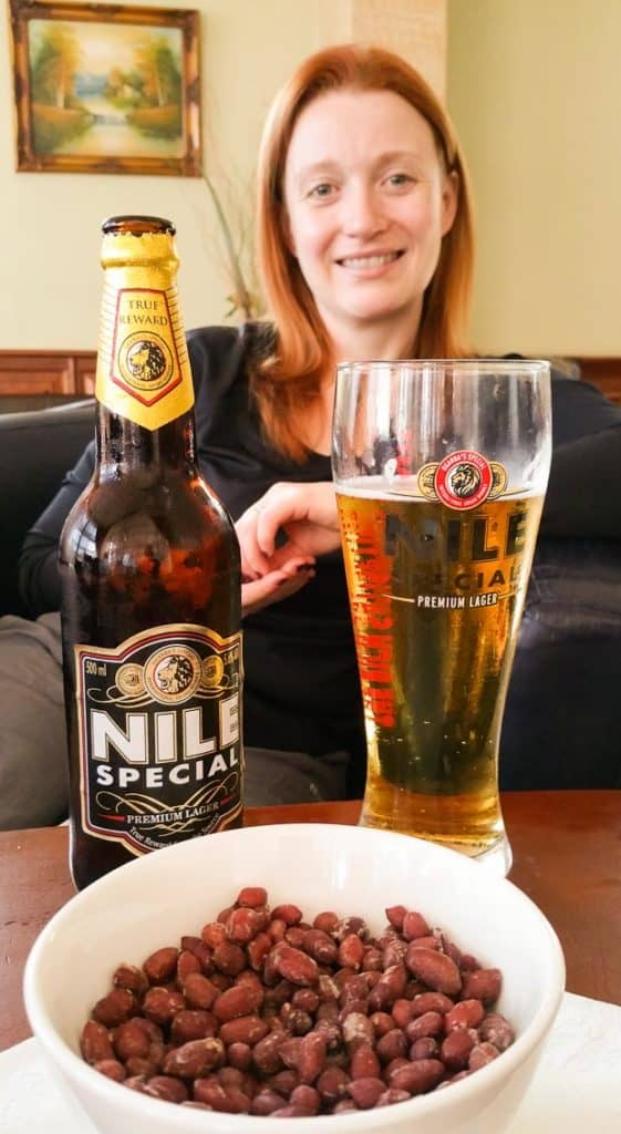A bottle of Nile Special beer with a glass beside and Lynne Lockier in the background. Hotel Sojovalo Kampala Uganda.