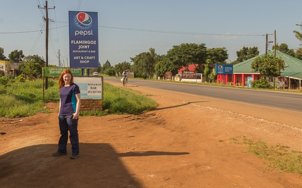 Lynne standing at The Equator with road through The Equator in the background.