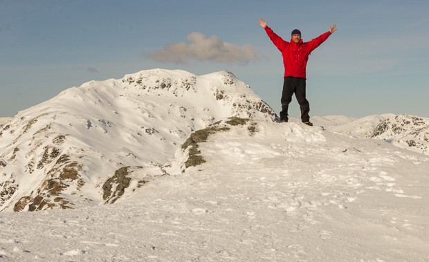 Mike standing with his arms in the air at the summit of Beinn Tulaichean.