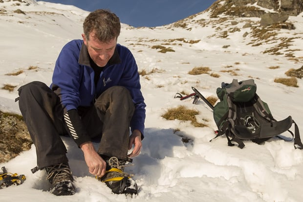 Mike putting on his crampons on the snowline of Beinn Tulaichean.