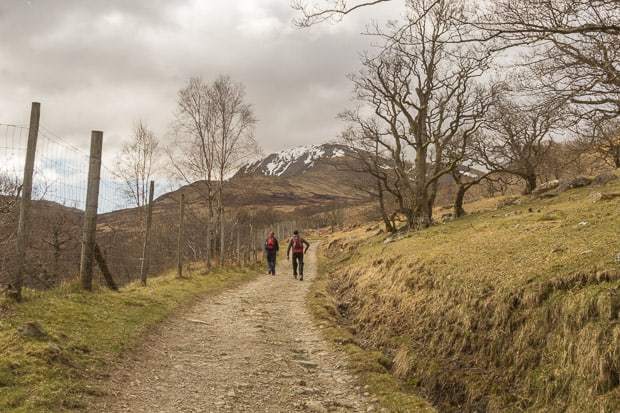 Liam Innes and Lynne Lockier in the distance on the path to Vorlich with snow on mountains in the background.
