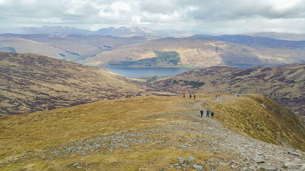 Looking back down the path with lots of other walkers following and Loch Earn in the distance.