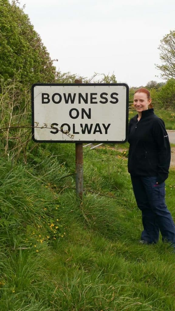 Lynne Lockier standing beside Bowness on Solway sign post.