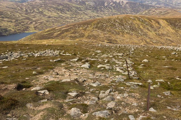 View looking down path and boundary line close to summit of Carn an t-Sagairt Mor.