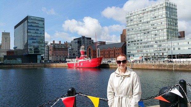 """Lynne Lockier with a lightship berthed in Liverpool in the background with """"bar"""" written on the side of it."""