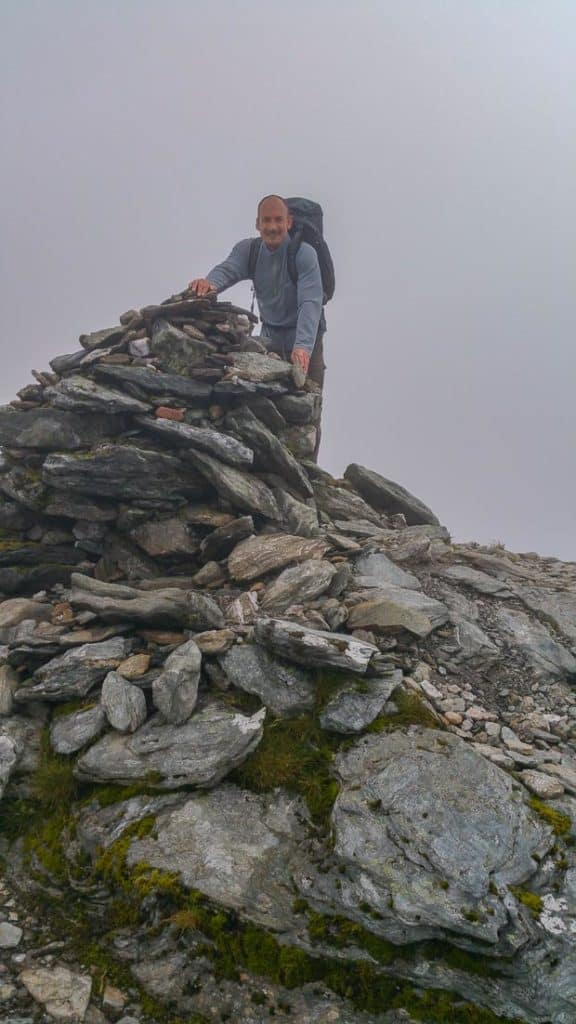 Neil Lockier standing at the summit of Cruach Ardrain hands resting on the summit cairn.