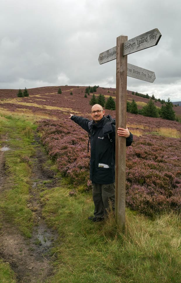 Southern Upland Way signpost at the top of Minchmoor Road. Neil Lockier pointing the way to The Three Brethren.