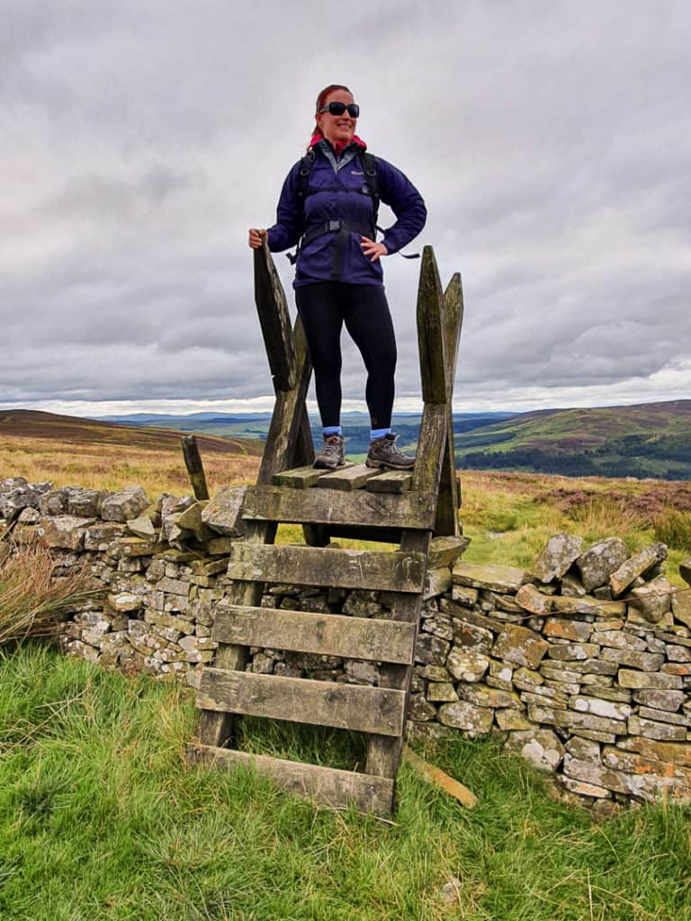 Lynne climbing over wall using a stile to reach the Southern Upland Way path.