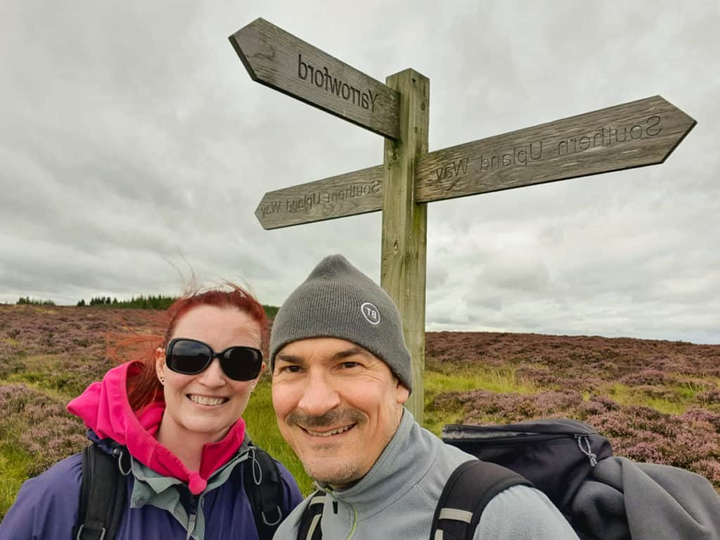 Neil and Lynne standing beside Southern Upland Way sign post.