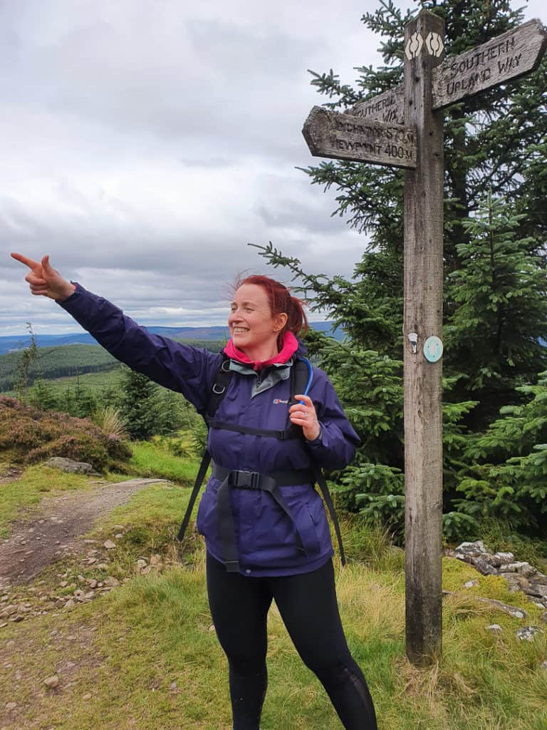 Lynne at the Minch Moor sign post pointing upward to the summit route.
