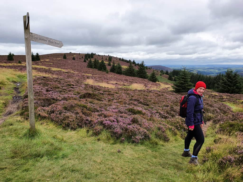 Sign post pointing down Minch Moor Road with Lynne already beginning the descent.